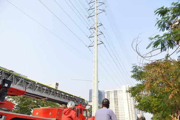 Cảnh sát đưa xe thang và đệm hơi ứng cứu thanh niên cố thủ trên cột điện cao thế - Ảnh 2.