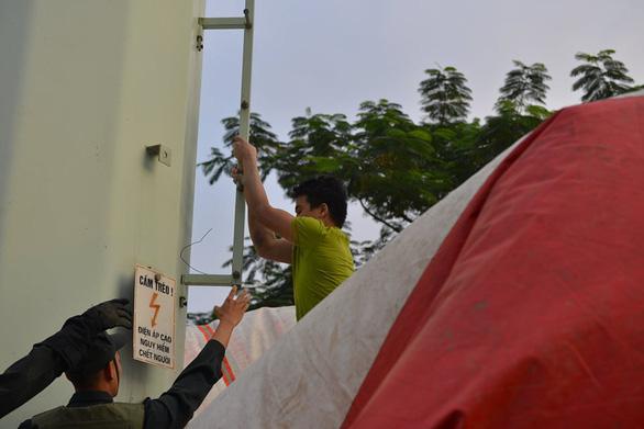 Cảnh sát đưa xe thang và đệm hơi ứng cứu thanh niên cố thủ trên cột điện cao thế - Ảnh 6.