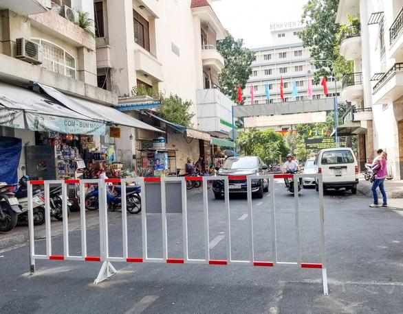 Dựng rào chắn đường vô chung cư để đối phó xe hơi đậu tràn lan - Ảnh 1.