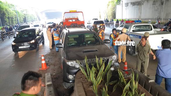 Xe hơi sụp vó ngay cửa hầm Thủ Thiêm, ứng cứu thì tài xế bỏ xe chạy - Ảnh 1.