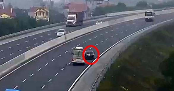 Liều lĩnh chạy lùi trên cao tốc, xe con suýt bị xe khách đâm - Ảnh 1.