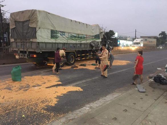 CSGT cùng người dân giúp tài xế thu gom ngô đổ ra đường sau tai nạn - Ảnh 1.