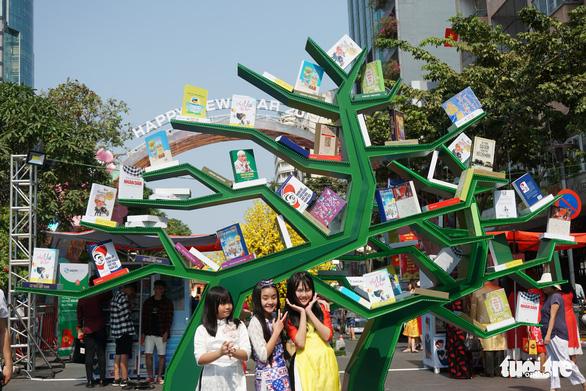 Nhiều gia đình ra đường hoa Nguyễn Huệ ngắm hoa, đọc sách - Ảnh 4.