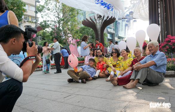 Nhiều gia đình ra đường hoa Nguyễn Huệ ngắm hoa, đọc sách - Ảnh 6.