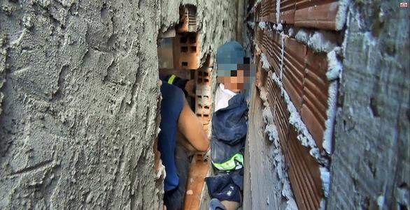 Cảnh sát cứu bé trai 7 tuổi kẹt giữa hai vách tường - Ảnh 1.