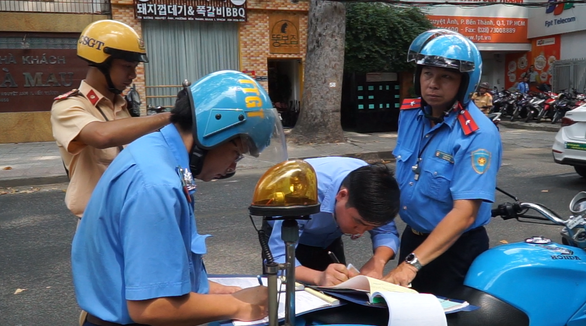 Ra quân xử phạt xe chở khách vi phạm ở Q.1, TP.HCM - Ảnh 1.