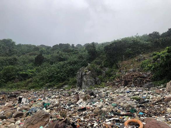Hàng chục bạn trẻ leo lên bãi rác khủng ở Đá Đen dọn rác trong mưa - Ảnh 1.