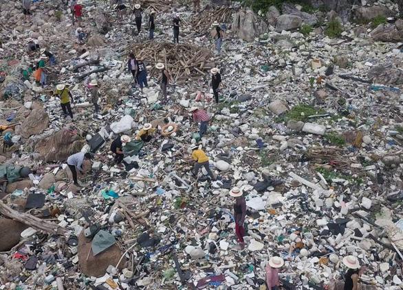 Hàng chục bạn trẻ leo lên bãi rác khủng ở Đá Đen dọn rác trong mưa - Ảnh 2.