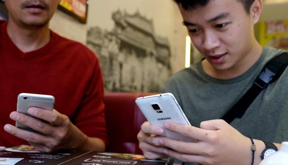 Không ít người lớn đang nghiện nặng smartphone - Ảnh: NAM TRẦN