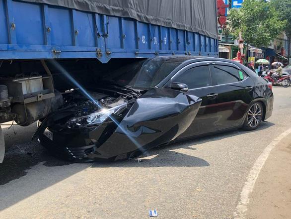 Ôtô 4 chỗ bị cuốn vào gầm xe tải, tài xế thoát chết - Ảnh 2.