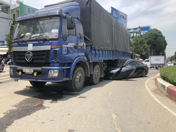 Ôtô 4 chỗ bị cuốn vào gầm xe tải, tài xế thoát chết - Ảnh 1.
