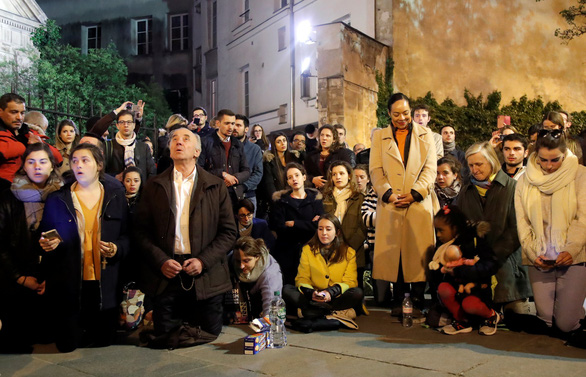 Người dân Paris quỳ khóc, cầu nguyện khi trái tim của Paris bốc cháy - Ảnh 1.