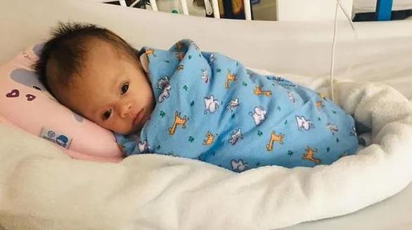 Em bé bị treo trên cây ở Việt Nam hồi phục kỳ diệu ở Bệnh viện Singapore - Ảnh 2.