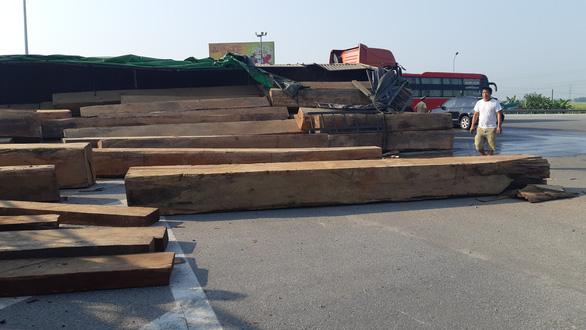 Xe chở gỗ lật giữa đường, nhiều người hú vía - Ảnh 2.