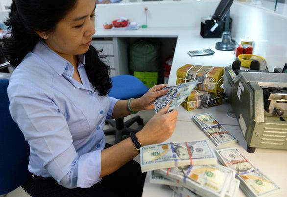 Tỉ giá biến động liên tục, Ngân hàng Nhà nước giảm tỉ giá trung tâm - Ảnh 1.