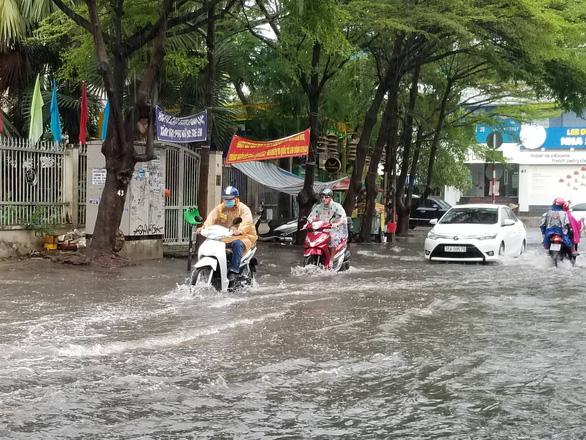 Chiều chủ nhật mưa rơi, người dân TP.HCM lại bì bõm lội nước - Ảnh 1.