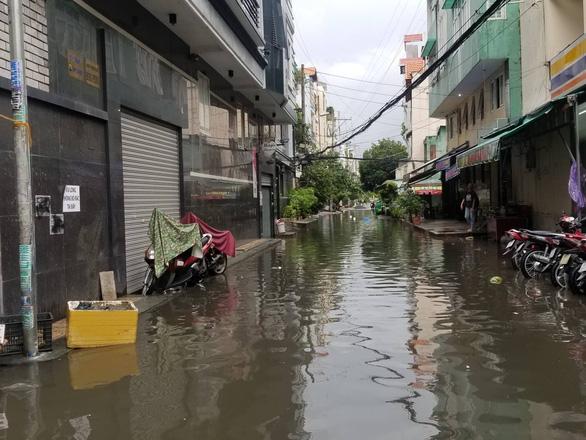Chiều chủ nhật mưa rơi, người dân TP.HCM lại bì bõm lội nước - Ảnh 4.