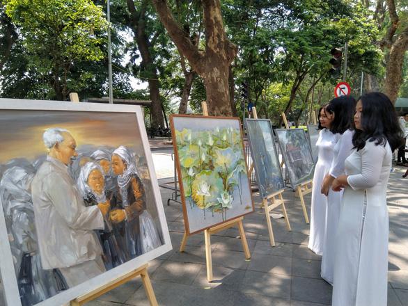 Xem tranh vẽ Bác của Tô Ngọc Vân, Mai Văn Hiến bên bờ hồ Gươm - Ảnh 1.