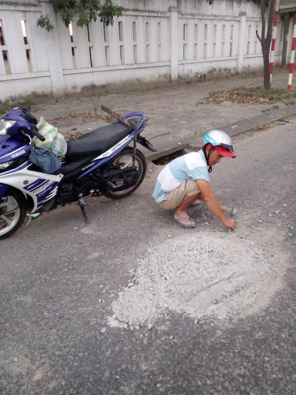 Hai thợ nề đục đẽo dẹp khối bêtông đổ giữa đường để xe không tai nạn - Ảnh 1.