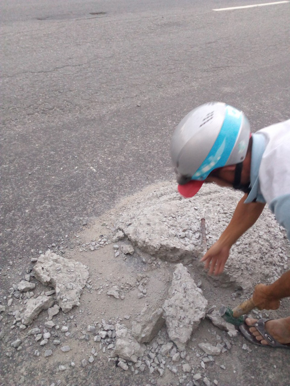 Hai thợ nề đục đẽo dẹp khối bêtông đổ giữa đường để xe không tai nạn - Ảnh 2.