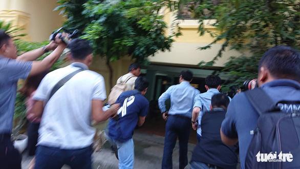 Ảnh ông Nguyễn Hưu Linh bị phóng viên quây kín khi đến tòa.