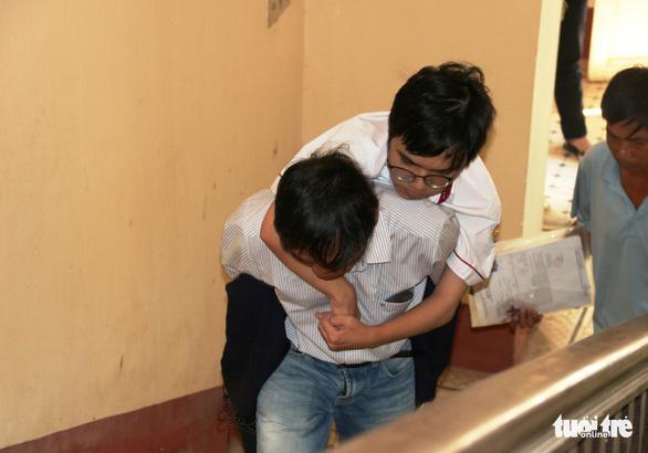 Cha mang chân giả cõng con lên phòng thi để động viên con - Ảnh 1.