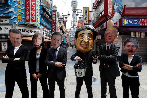 Các nhà lãnh đạo G20 xuống đường biểu tình ở Osaka - Ảnh 1.
