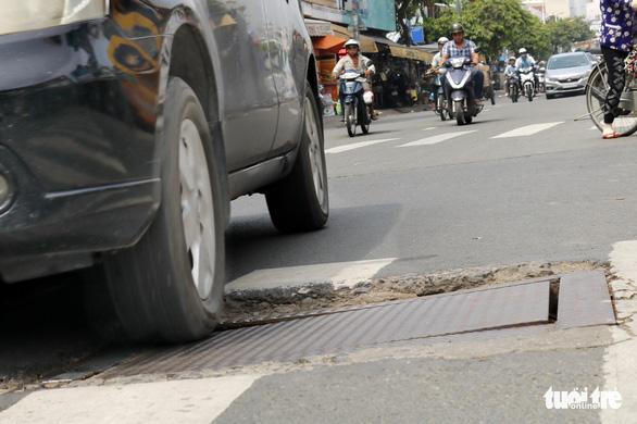 Phập phồng đi ngang những nắp cống ỡm ờ trên mặt đường Sài Gòn - Ảnh 1.