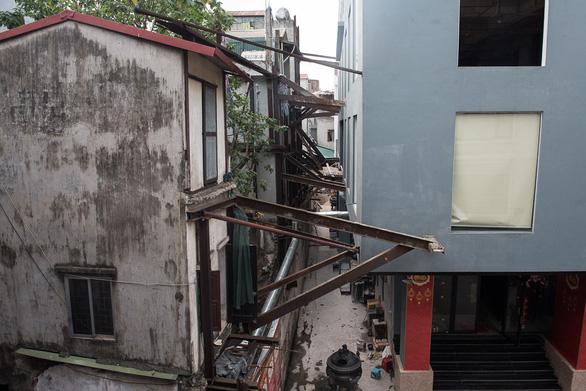 Hàng chục ngôi nhà chống nạng sắt vào chung cư ở Hà Nội - Ảnh 1.