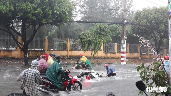 Mưa lớn, nước chảy xiết cuốn ngã nhiều xe máy ở Thủ Đức - Ảnh 2.