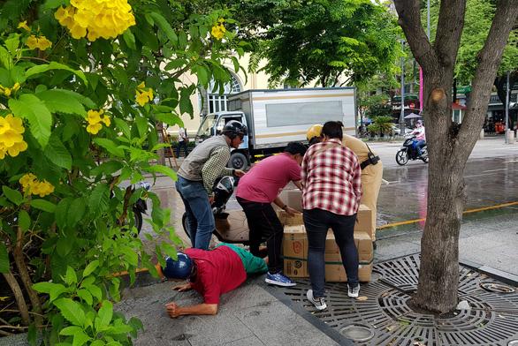 Xe bồn tưới nước đi qua, xe máy ngã nhào trên phố đi bộ Nguyễn Huệ - Ảnh 1.