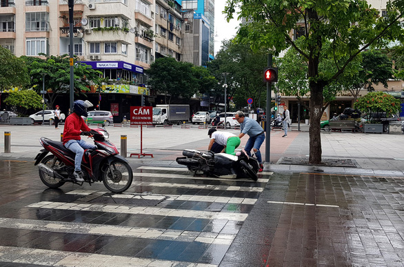 Xe bồn tưới nước đi qua, xe máy ngã nhào trên phố đi bộ Nguyễn Huệ - Ảnh 3.