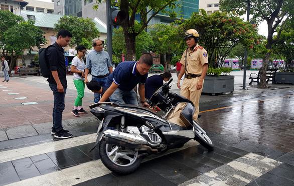 Xe bồn tưới nước đi qua, xe máy ngã nhào trên phố đi bộ Nguyễn Huệ - Ảnh 4.