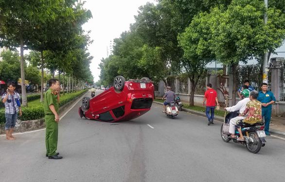 Xe hơi lật ngửa giữa đường, nữ hành khách nhập viện cấp cứu - Ảnh 1.