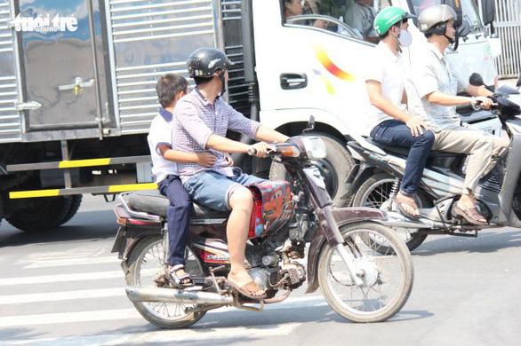 Chở trẻ em không đội mũ bảo hiểm bị phạt nghiêm từ tháng 9 - Ảnh 1.