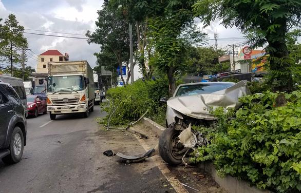 Xe 4 chỗ mất lái băng ngang quốc lộ 1, biến dạng khi tông xe tải - Ảnh 1.