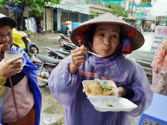 Bạn trẻ Phú Quốc phát cơm nóng cho bà con nghèo ngày mưa bão - Ảnh 1.