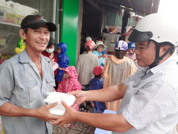 Bạn trẻ Phú Quốc phát cơm nóng cho bà con nghèo ngày mưa bão - Ảnh 3.