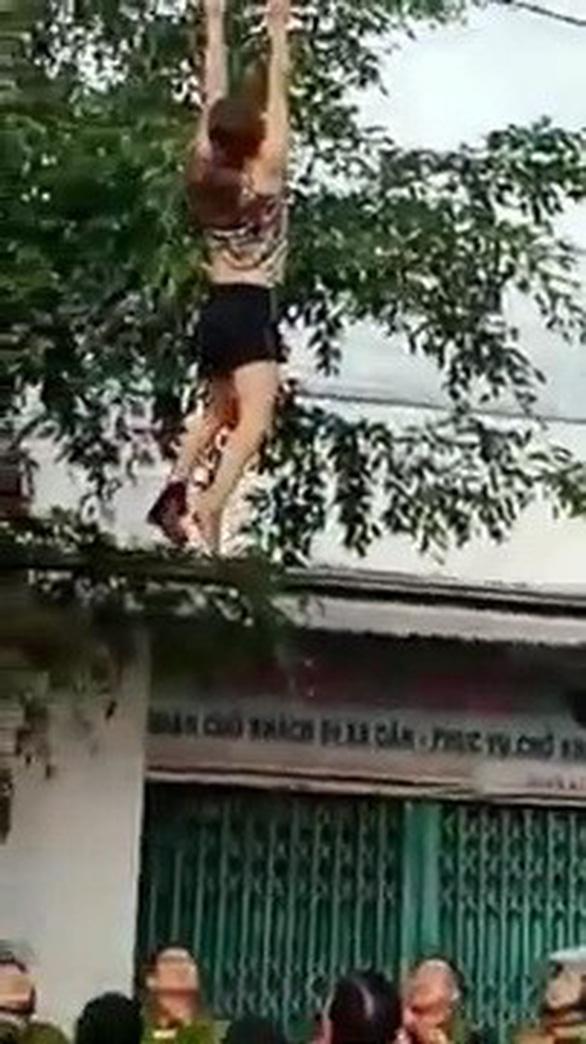 Cứu người phụ nữ nghi ngáo đá làm xiếc trên dây điện - Ảnh 1.