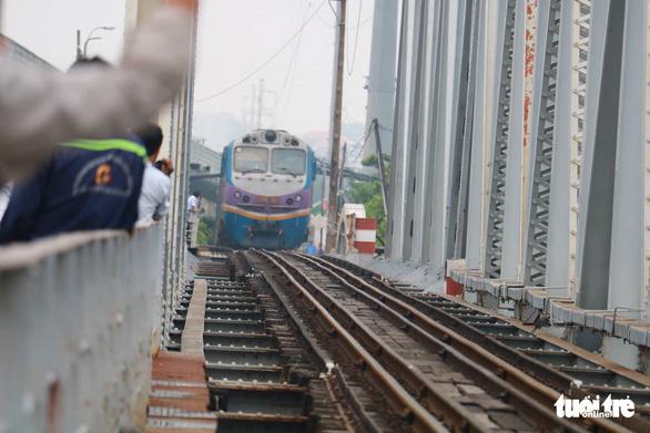 Video chuyến tàu cuối cùng qua cầu đường sắt Bình Lợi 117 tuổi - Ảnh 2.
