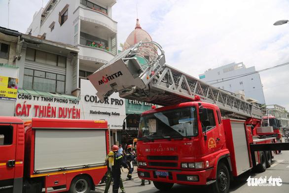 Cứu cụ bà ngất xỉu và 2 người kẹt trên sân thượng trong vụ cháy ở quận 5 - Ảnh 1.