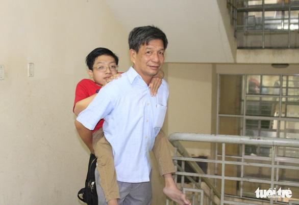 14 năm đi học trên vai cha vì chứng xương quằn - Ảnh 1.