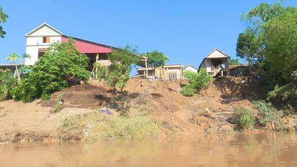 Sạt lở nghiêm trọng sau lũ, nhiều nhà có nguy cơ chìm xuống sông - Ảnh 1.