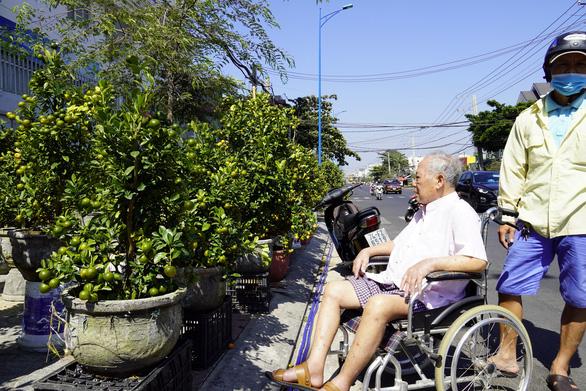 Con dâu, cháu nội đẩy xe lăn đưa cụ ông 93 tuổi đi mua hoa tết - Ảnh 2.