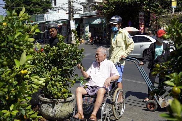 Con dâu, cháu nội đẩy xe lăn đưa cụ ông 93 tuổi đi mua hoa tết - Ảnh 1.