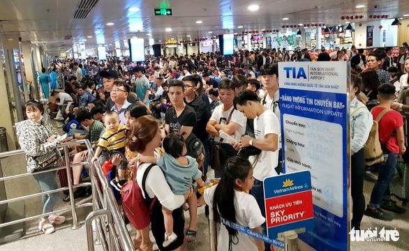 Máy bay liên tục hoãn chuyến, hành khách nằm, ngồi la liệt ở Tân Sơn Nhất - Ảnh 2.