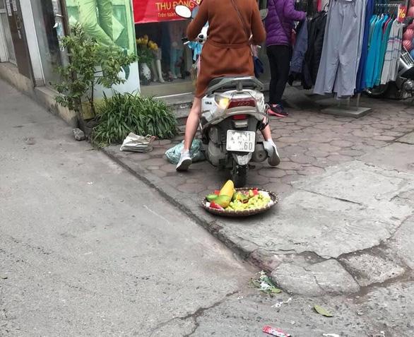 Người phụ nữ cán xe máy qua mẹt trái cây của chị bán hàng rong - Ảnh 2.