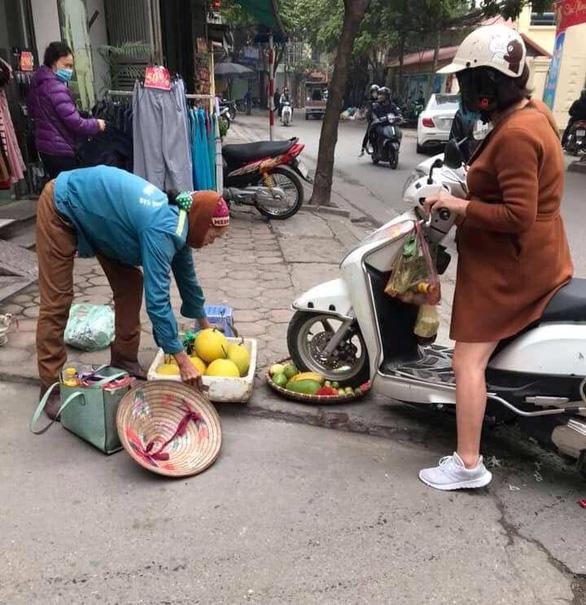 Người phụ nữ cán xe máy qua mẹt trái cây của chị bán hàng rong - Ảnh 1.