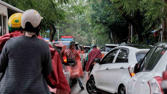 Mồng 1 tết, Hà Nội vừa ngớt lại mưa to, cuộc du xuân dang dở - Ảnh 3.