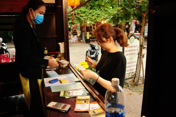 Du khách nước ngoài thăm Hội An vui vì được phát khẩu trang miễn phí - Ảnh 1.